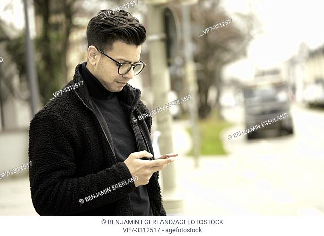 young man using phone in city, in Munich, Germany