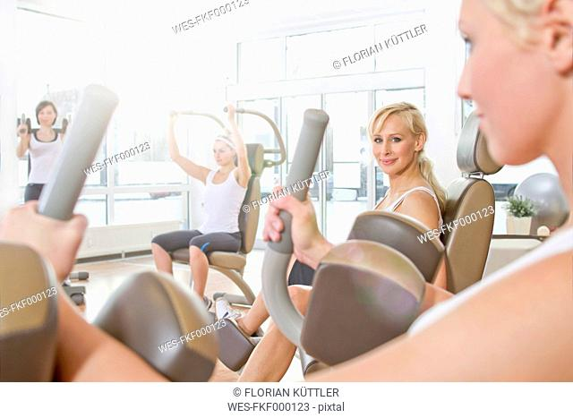 Germany, Brandenburg, Womens exercising in gym, smiling