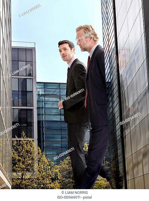 Oversized businessmen walking amongst skyscrapers, low angle view