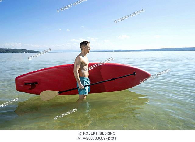 Mature man carrying paddleboard in the lake, Bavaria, Germany