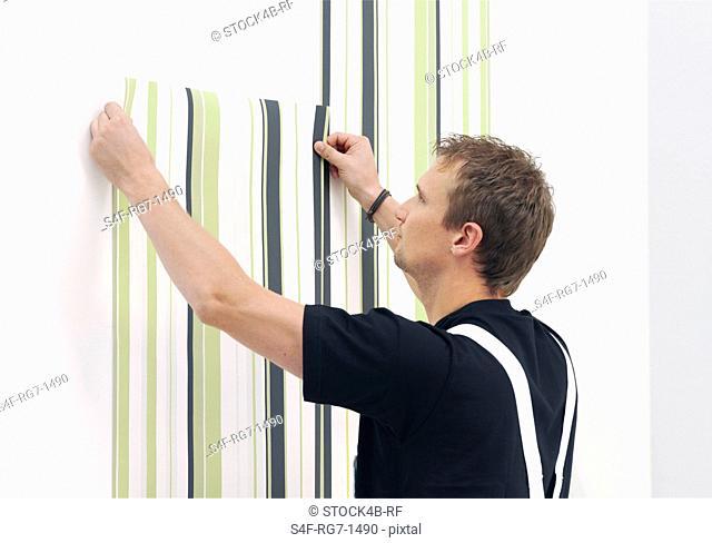 Man wallpapering