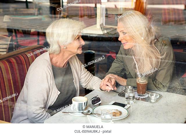 Mother and daughter sitting together in cafe, holding hands, seen through cafe window
