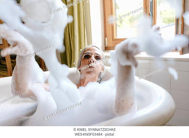Portrait of woman in bathtub playing with foam