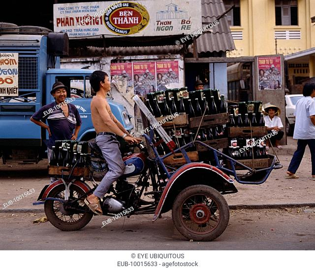 Man riding motorbike laden with beer bottles. Advertising posters