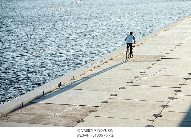 Young man riding bike on waterfront promenade at the riverside