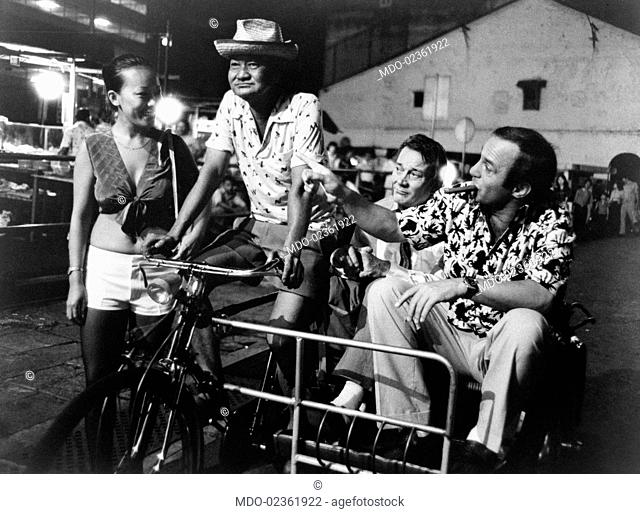 An Asian man carrying on a rickshaw American actor Ben Gazzara and British actor Denholm Elliott in Saint Jack. 1979