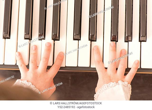 Close up of hands of child playing the piano. Top view of little girl practicing on her music