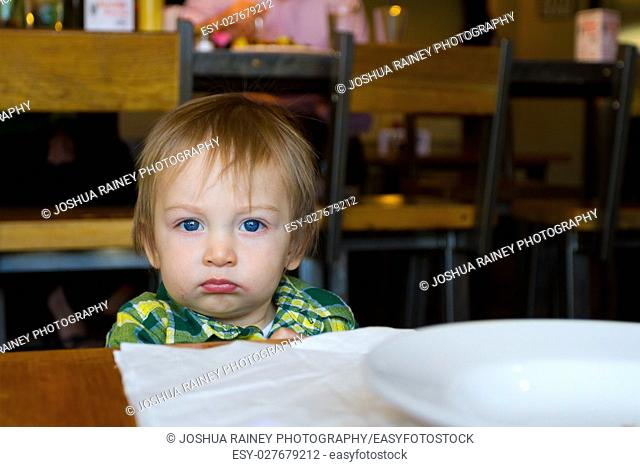 A young one year old toddler boy plays with a napkin at a restaurant while waiting for his food