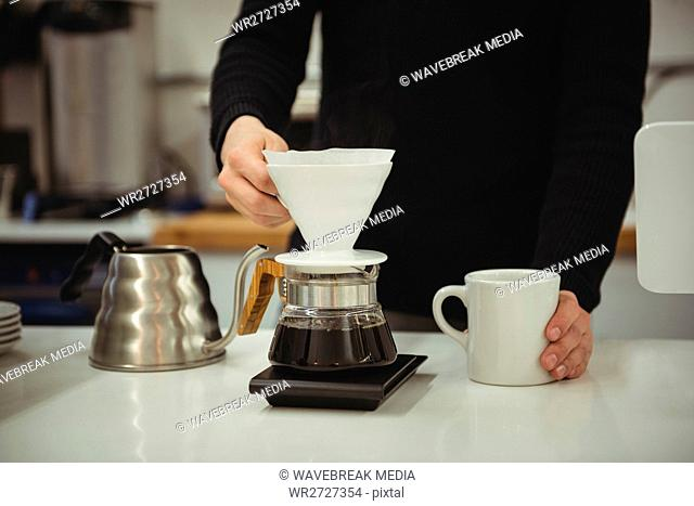 Man holding filter funnel and coffee mug
