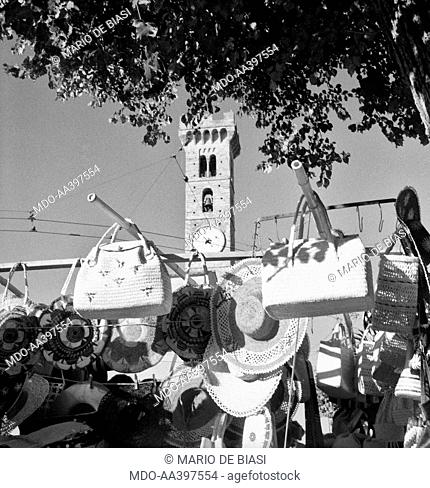 The bell tower of the San Romolo cathedral standing behind a bags stall. Fiesole, 1950s