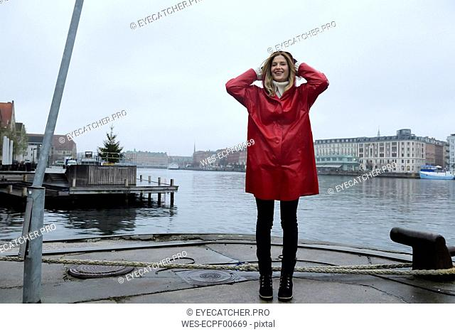 Denmark, Copenhagen, happy woman at the waterfront in rainy weather