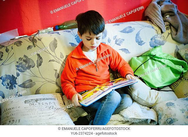 Child reads a book on the couch
