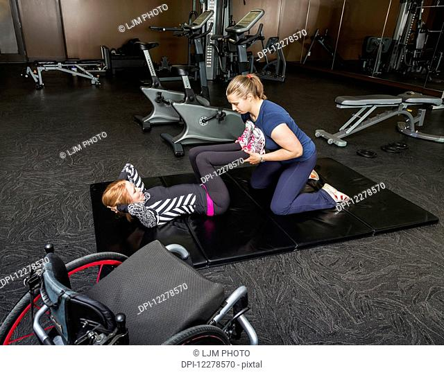Physiotherapist assisting young woman with spinal cord injury in performing double leg press exercises; Edmonton, Alberta, Canada