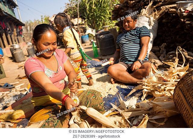 Woman schucking corn in Ramkot Village, a traditional Newari village, Bandipur, Nepal