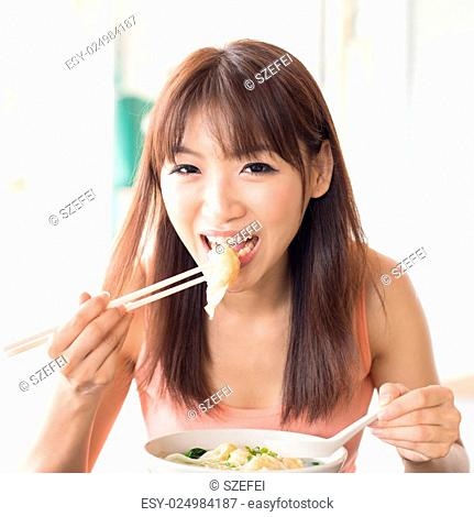Asian girl eating delicious dumplings at Chinese restaurant. Young woman living lifestyle