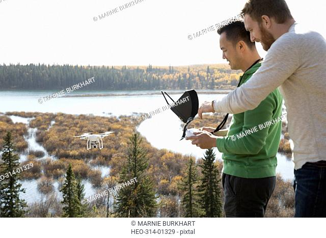 Male friends with drone equipment overlooking lake