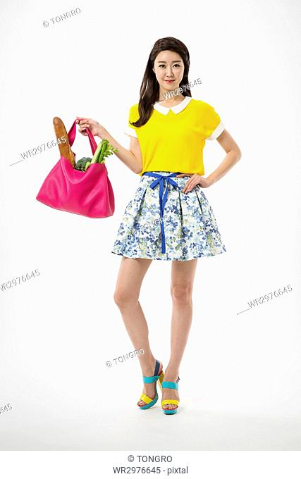 Young smiling woman in casual clothes posing holding a bag