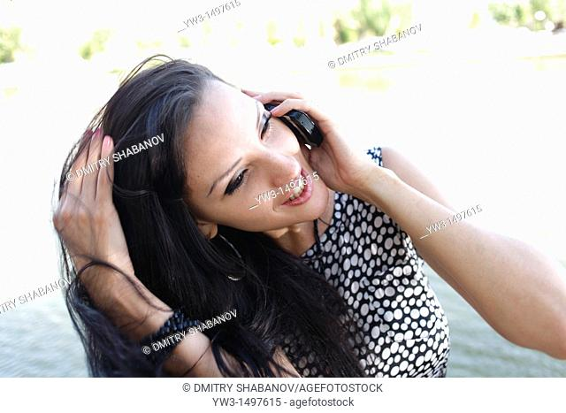 25 year old pretty woman outdoors talking by cell phone