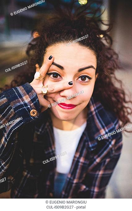 Portrait of woman looking at camera through fingers