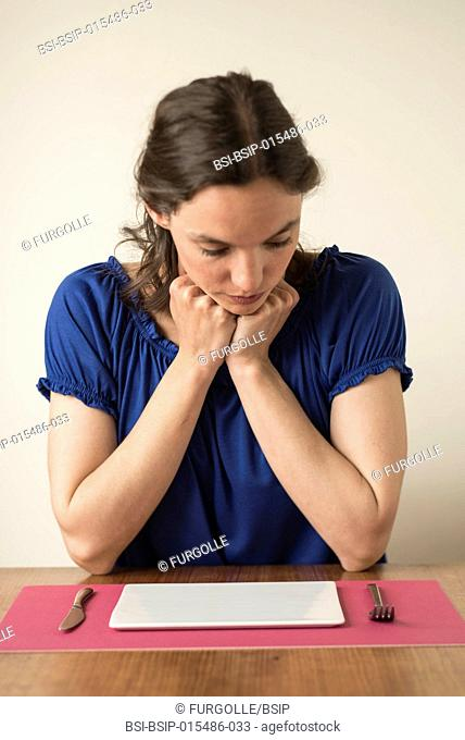 Woman looking at an empty plate