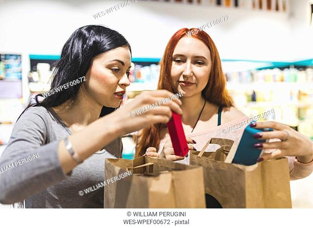 Shop assistant and customer packing products into paper bag in a cosmetics shop