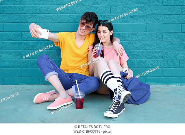 Young couple with soft drinks taking selfie with smartphone in front of blue brick wall