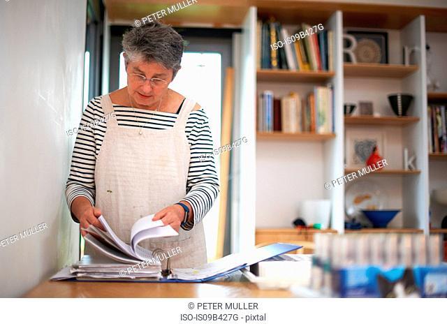 Senior woman in kitchen, looking through file