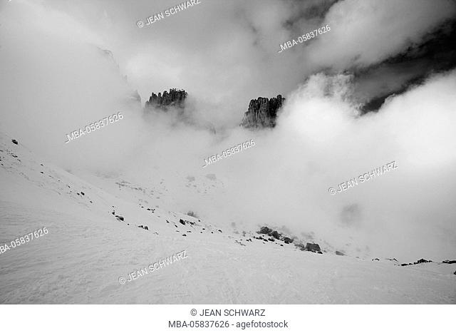 Clouds hang between the mountains of the Dolomites