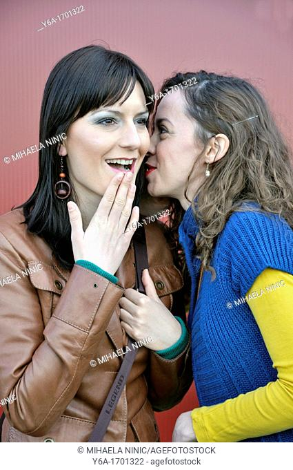 Young women whispering in friend's ear outdoors
