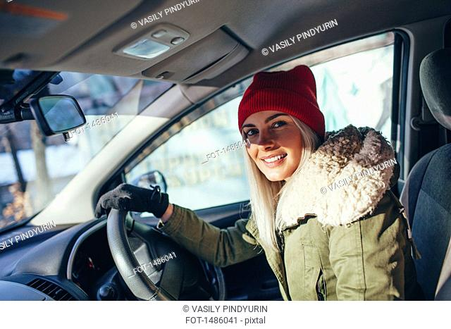 Portrait of happy woman in warm clothing driving car