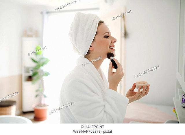 Smiling woman in bathrobe applying make-up in the morning at home