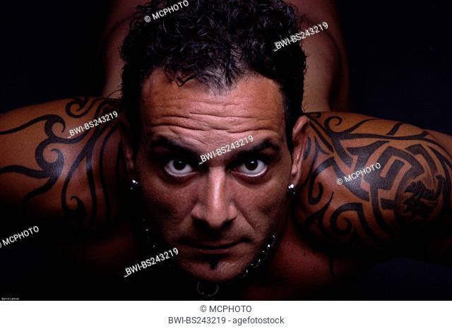 posing tatooed muscular man