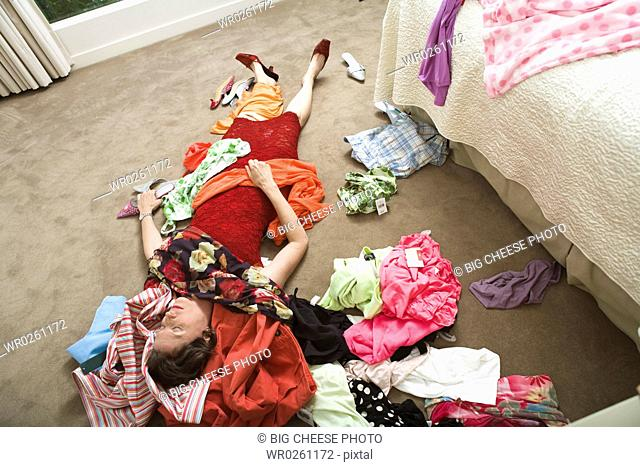 Woman on bedroom floor buried under clothing