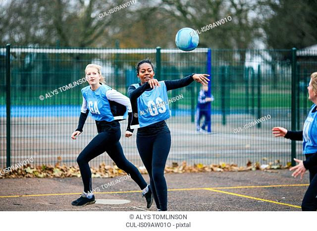 Female netball team playing match on netball court