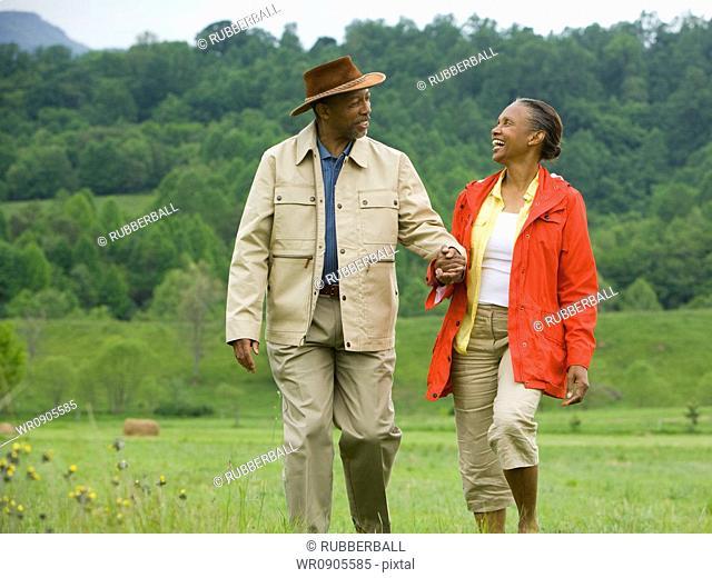 Senior man and a senior woman walking in a field