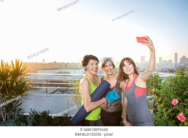 Women taking cell phone selfie on urban rooftop