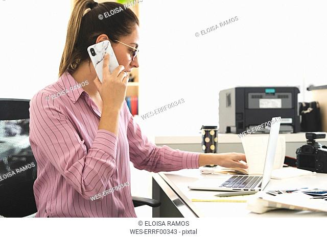 Designer working in office, using laptop, talking on the phone