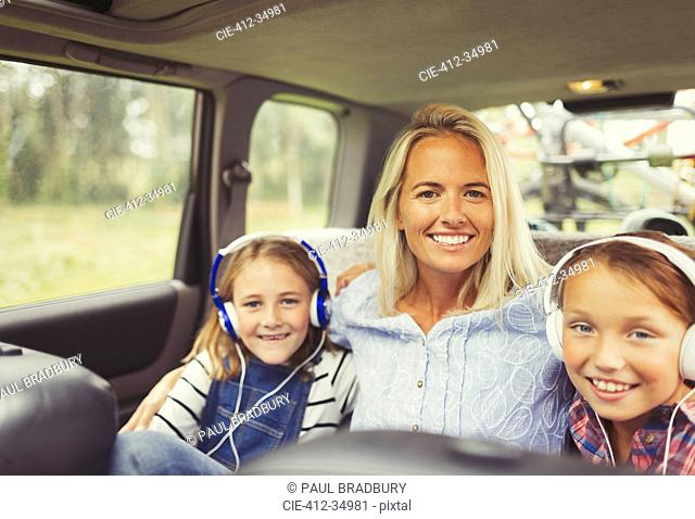 Portrait smiling mother and daughters wearing headphones in back seat of car