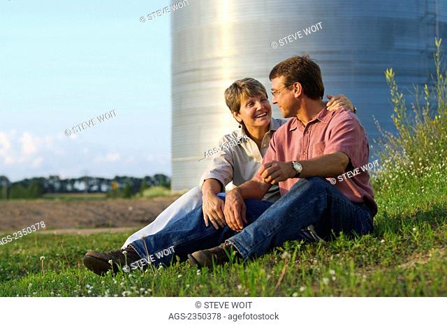Agriculture - Husband and wife farmers sit together while sharing some personal moments together, with grain bins in the background / Minnesota, USA