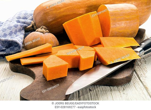 peeled and sliced butternut pumpkin with knife on wooden board