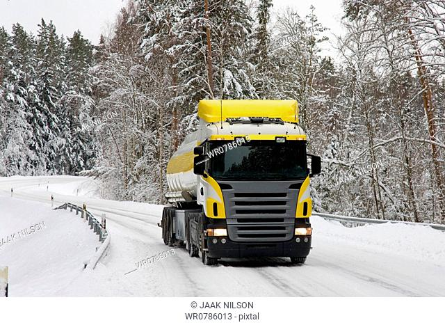 Winter snow on a forest road. Trees. A large Estonian Fuel Company Olerex Gasoline truck on the road