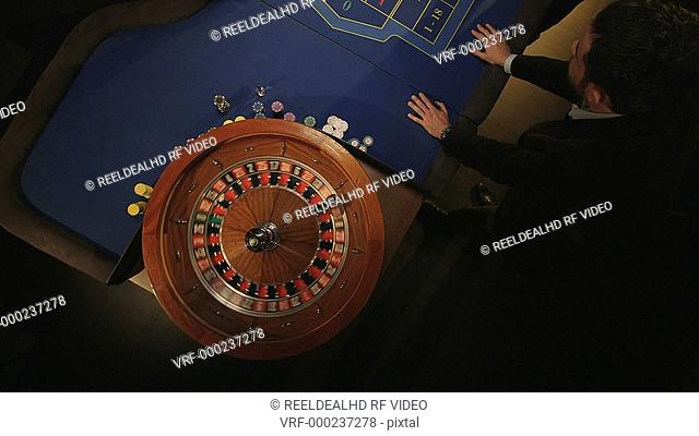 Smartly dressed players place their bets on the Roulette Table