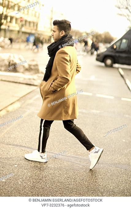 young fashionable man walking on street in city, male blogger with style, in Munich, Germany