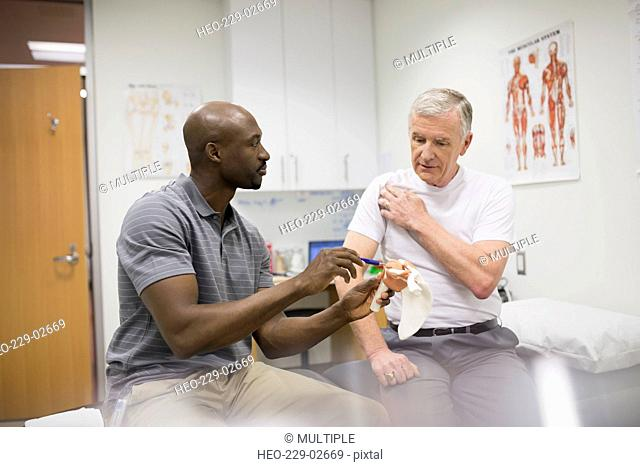 Physical therapist explaining shoulder pain patient with model