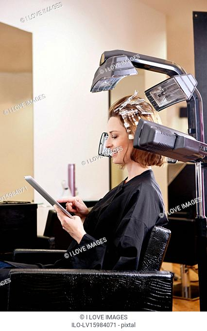 A female client using an digital tablet whilst she has her hair coloured in a hairdressing salon