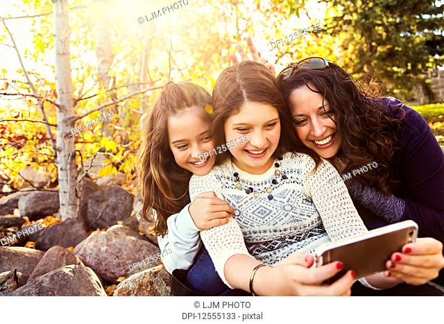 A mom and her two daughters taking a self-portrait while resting during a family outing in a city park on a warm fall day; Edmonton, Alberta, Canada
