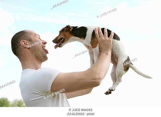 Man sticking out tongue at small dog outdoors