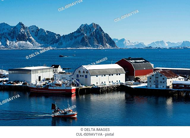Fishing boat sailing by industrial buildings, Svolvaer, Lofoten Islands, Norway
