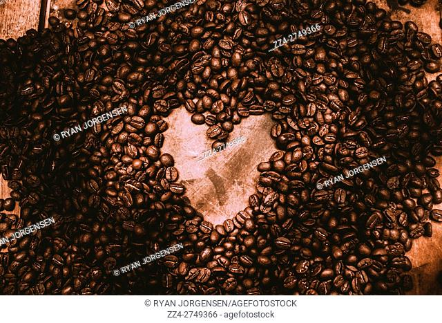 Rustic kitchen artwork on a spillage of roasted brew house beans with heart shape center. Home is where the coffee is