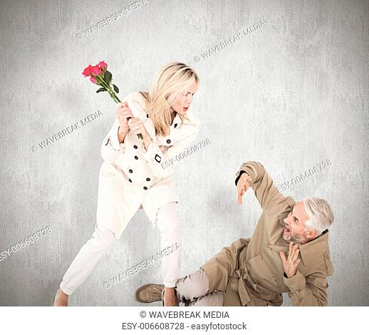 Composite image of angry woman attacking partner with rose bouquet